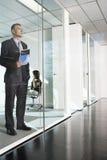 Parete di Standing Against Glass dell'uomo d'affari Fotografie Stock
