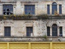 Parete di vecchia costruzione con le aperture della finestra e vetro rotto nei telai, nella priorità alta un recinto giallo, Kiev Immagine Stock Libera da Diritti