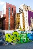 Parete dipinta dai graffiti con le costruzioni di affari sui precedenti Fotografie Stock