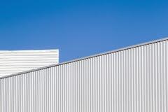 Parete e tetto ondulati della lamiera sottile contro cielo blu Magazzino moderno o stoccaggio Sguardo industriale esterno Digitah fotografia stock libera da diritti