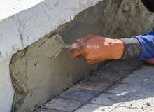 Parete funzionante dell'uomo per cemento con la cazzuola Immagini Stock Libere da Diritti