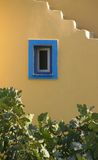Parete gialla con la finestra blu Immagine Stock