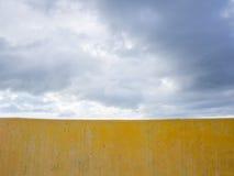 Parete gialla e cielo tempestoso delle nuvole nel fondo Immagine Stock Libera da Diritti