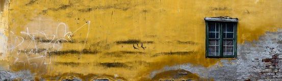 Parete gialla rovinata della casa con una finestra immagine stock