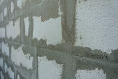 Parete grigia dei blocchetti di schiuma sulla soluzione glutinosa fotografia stock
