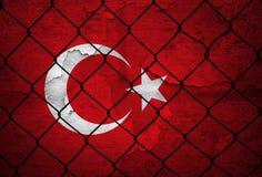 Parete incrinata della bandiera della Turchia con il fondo del recinto di filo metallico fotografia stock libera da diritti
