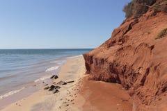 Parete laterale rossa accanto alla spiaggia alla baia della bottiglia in Francois Peron National Park Fotografie Stock