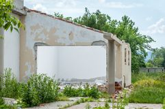 Parete nociva della casa o della costruzione civile domestica con il foro ed il tetto crollato distrutti dalla granata nella zona Immagine Stock Libera da Diritti