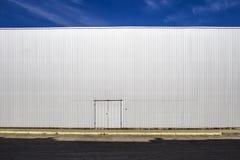 Parete ondulata della lamiera sottile con una porta, le ombre della via ed il cielo blu esterno Sguardo industriale Priorità bass Immagine Stock Libera da Diritti