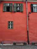 parete rossa con le finestre verdi Sibiu |La Romania Fotografia Stock Libera da Diritti