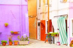 Pareti colourful tradizionali di vecchie case comuni con i vasi da fiori e la bicicletta vicino alla porta di entrata nell'isola  Fotografia Stock Libera da Diritti