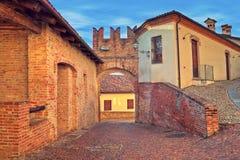 Pareti medievali del mattone rosso e della via Cobbled. Fotografie Stock
