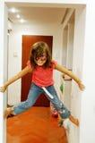 Pareti rampicanti della ragazza in casa fotografia stock