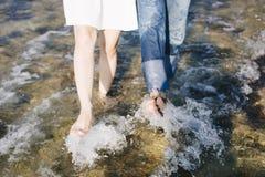 Parets fot går tillsammans på stranden arkivfoton