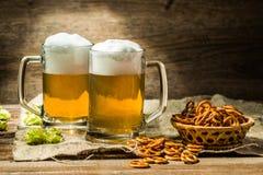 Parexponeringsglas av öl skummar med flygtur och kringlor Royaltyfria Bilder