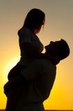 parförälskelse silhouettes solnedgångbarn Arkivbild