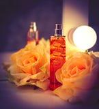 Parfüm in den schönen Flaschen und in den Blumen lizenzfreies stockbild