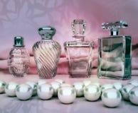 Parfüm in Glasflaschen und Perle auf rosa Hintergrund Lizenzfreie Stockfotos