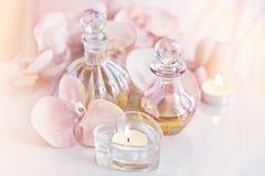 Parfüm und aromatische Ölflaschen umgeben durch Blumen und cand stockbilder