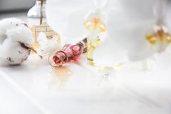 Parfüm- und Blumenbaumwolle und weiße Orchidee auf weißem Holztisch Lizenzfreie Stockfotos