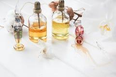 Parfüm- und Blumenbaumwolle und weiße Orchidee auf weißem Holztisch Stockfotos