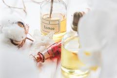 Parfüm- und Blumenbaumwolle und weiße Orchidee auf weißem Holztisch Stockfoto