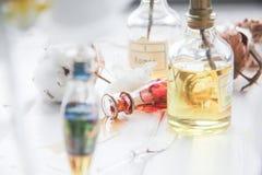 Parfüm- und Blumenbaumwolle und weiße Orchidee auf weißem Holztisch Lizenzfreies Stockfoto