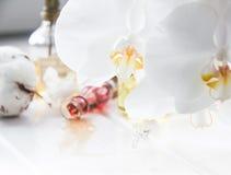 Parfüm- und Blumenbaumwolle und weiße Orchidee auf weißem Holztisch Lizenzfreies Stockbild