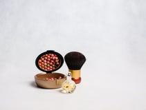 Parfüm und Rouge mit einer Bürste Stockfotografie