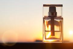 Parfümflasche auf Goldsonnenunterganghintergrund mit Kopienraum Lizenzfreie Stockbilder