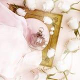 Parfümflasche, Rosen und Perlen gelegen auf den Falten des rosa Si Stockbild