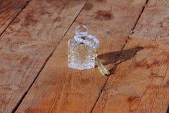 Parfümflasche und Perlen auf einem hölzernen Hintergrund Stockfotografie