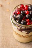 Parfait breakfast. Parfait-style healthy layered breakfast with yogurt,bilberry jam,fresh currant berries,muesli or granola in clear glass on linen clothed table Stock Images