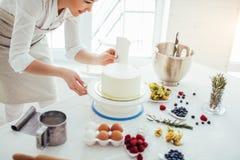 Parfait lissez chef tenant des agains d'un grattoir de banc verticalement le gâteau photo libre de droits