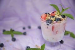 Parfait ? yaourt de granola avec les myrtilles et les fraises fra?ches sur un fond lilas clair Le concept de la consommation sain photos libres de droits