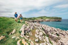 Parfotvandrarehandelsresande går på stenig kust för havet royaltyfri foto