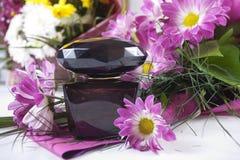 Parfum avec des fleurs autour de lui Image stock
