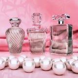 Parfum dans bouteilles en verre et perle sur le fond rose Image libre de droits