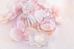 Parfum en aromatische die oliënflessen door bloemen wordt omringd en cand royalty-vrije stock foto's