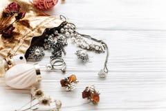 Parfum et montre chers de luxe de bijoux sur le woode rustique blanc Photographie stock libre de droits