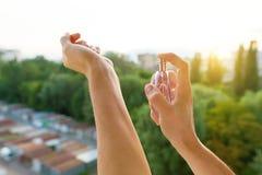Parfum in handen, achtergrondavondzonsondergang, stadssilhouet stock afbeelding