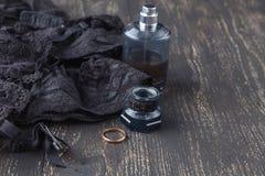 Parfum och svart damunderkläder för en romantisk afton royaltyfri fotografi