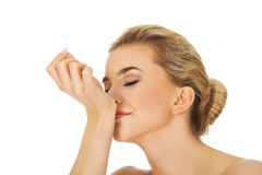 Parfum sentant de jeune femme sur son poignet Image stock