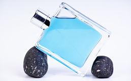 Parfume bottle. Blue parfume bottle and stones stock images