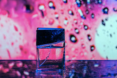 Parfume bottle on the pink background. With water drops Royalty Free Stock Photo