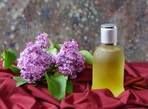 Parfume en una botella con las flores de la lila Fotografía de archivo