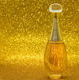 Parfume gold bokeh background glass bottle close-up macro texture. Dior parfume close-up macro bokeh background gold color celebrity love glitter shine stock images