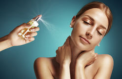 Parfume spray on a neck. Woman portrait with a hand with a boutle of parfume stock photo