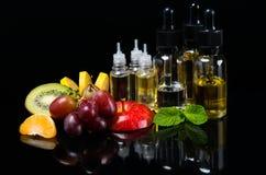 Parfumez le liquide dans les bulles entourées par le fruit mûr et la menthe fraîche images stock