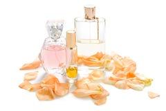 Parfumflessen met bloembloemblaadjes op lichte achtergrond Parfumerie, geurinzameling Vrouwentoebehoren stock afbeelding
